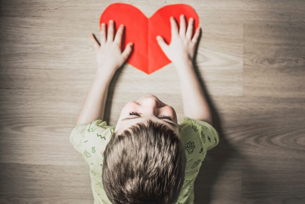 Garçon tenant un coeur rouge